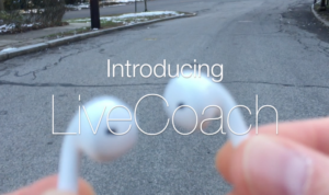 Promotional image of earbuds being held in an outdoor scene.