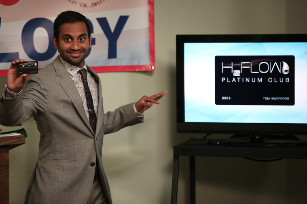 "Photograph of ""Parks and Rec"" character pointing at a television monitor as he explains Sparkle Points."