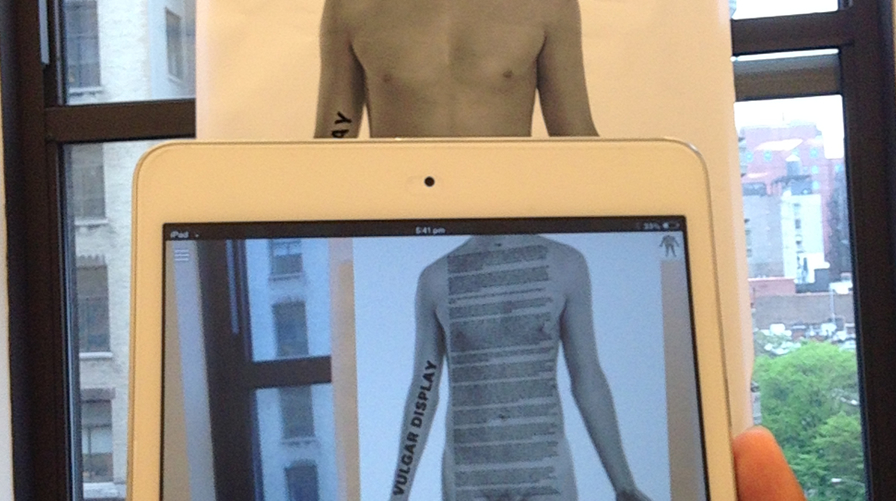 The image shows a tablet being held up in front of a photograph of a man's torso. The augmented reality experience on the tablet adds a text overlay to the torso, so the viewer can read the text as if it were printed on the torso.