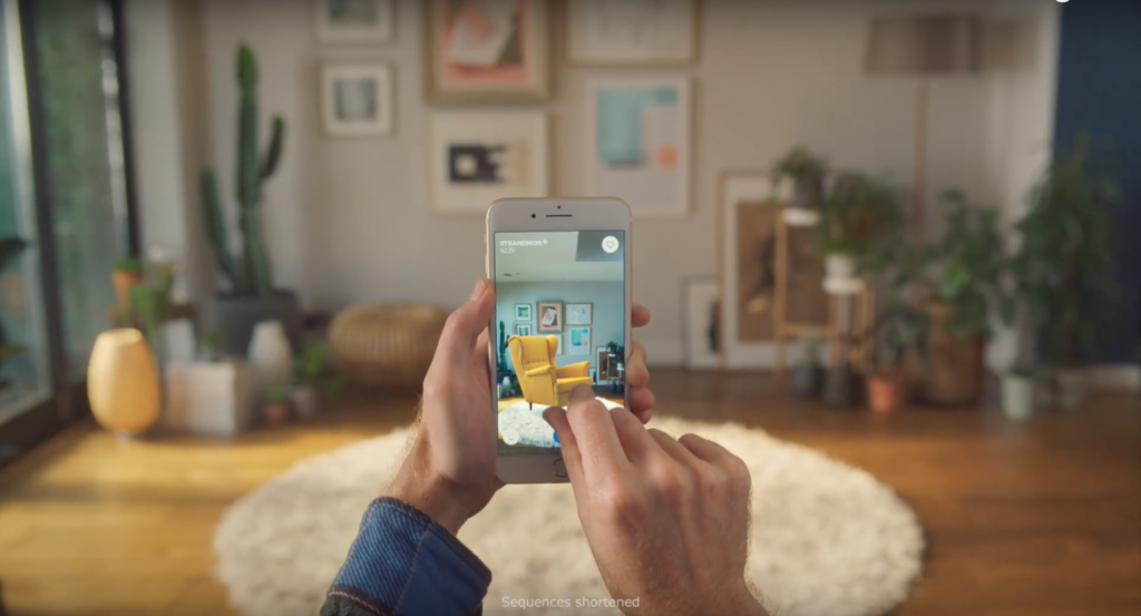 Image shows a person's hands holding a mobile phone. The person is in a living space, and the image on the phone is of that living space with an Ikea wing chair added to the scene.