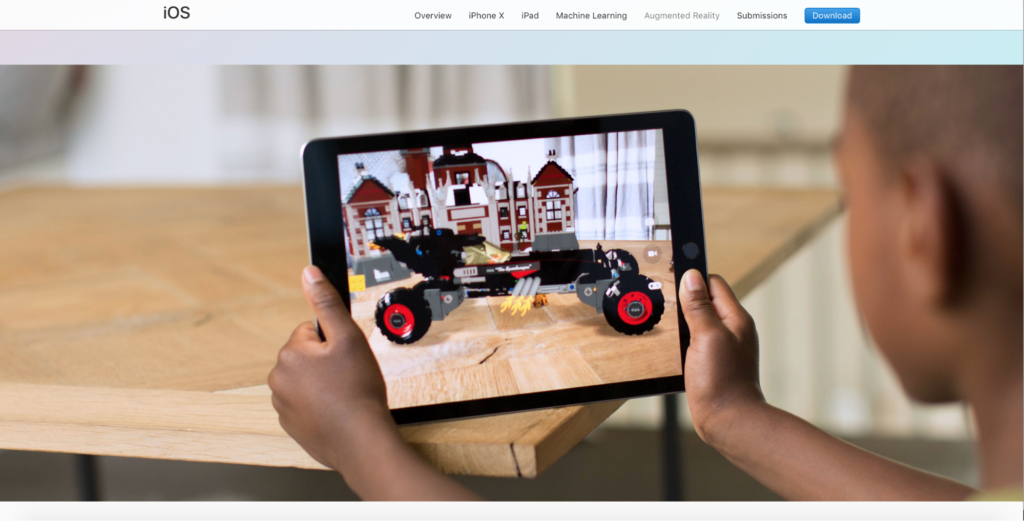 Image shows a child, seated at a table, holding a tablet. The image on the tablet appears to be a robotic car, viewed with AR as sitting on the table the child is at.