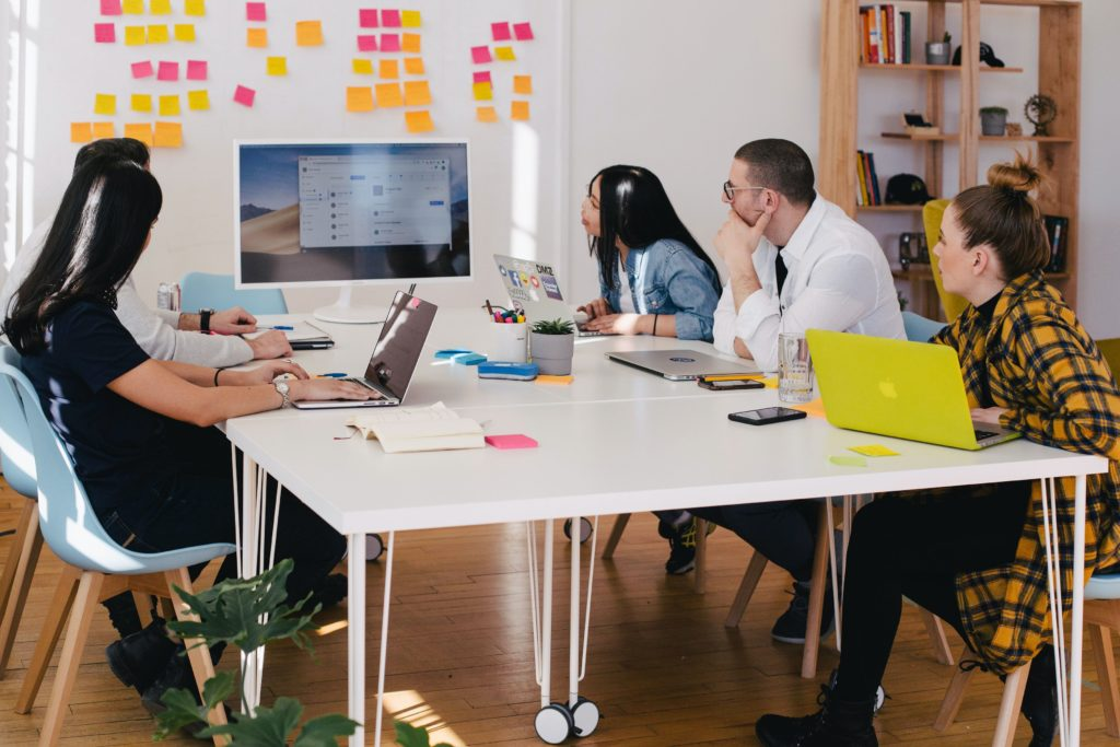 Photo of a team seated around a conference table collaborating on a project by You X Ventures on Unsplash.