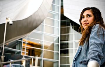 Image of a woman in a denim jacket standing in front of office buildings