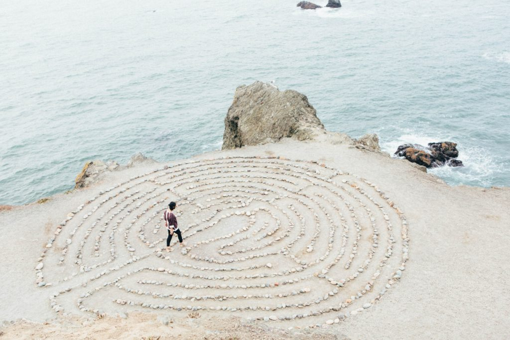 Person walking through a maze made of small stones so that it's easy to navigate.